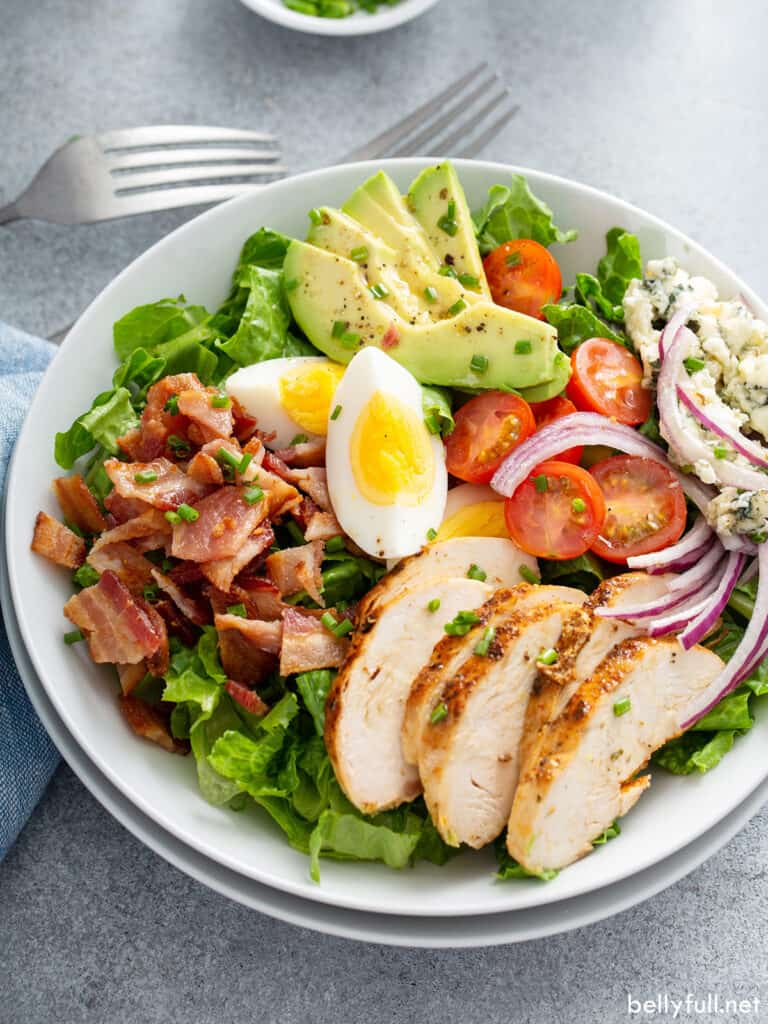 salad with chicken, bacon, and hard cooked eggs on white plate