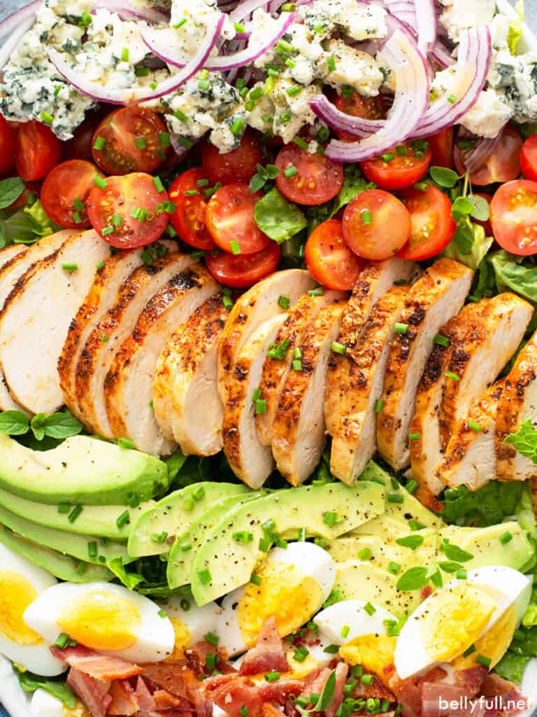 close up rows of roasted chicken, avocado, cherry tomatoes, and hard boiled eggs