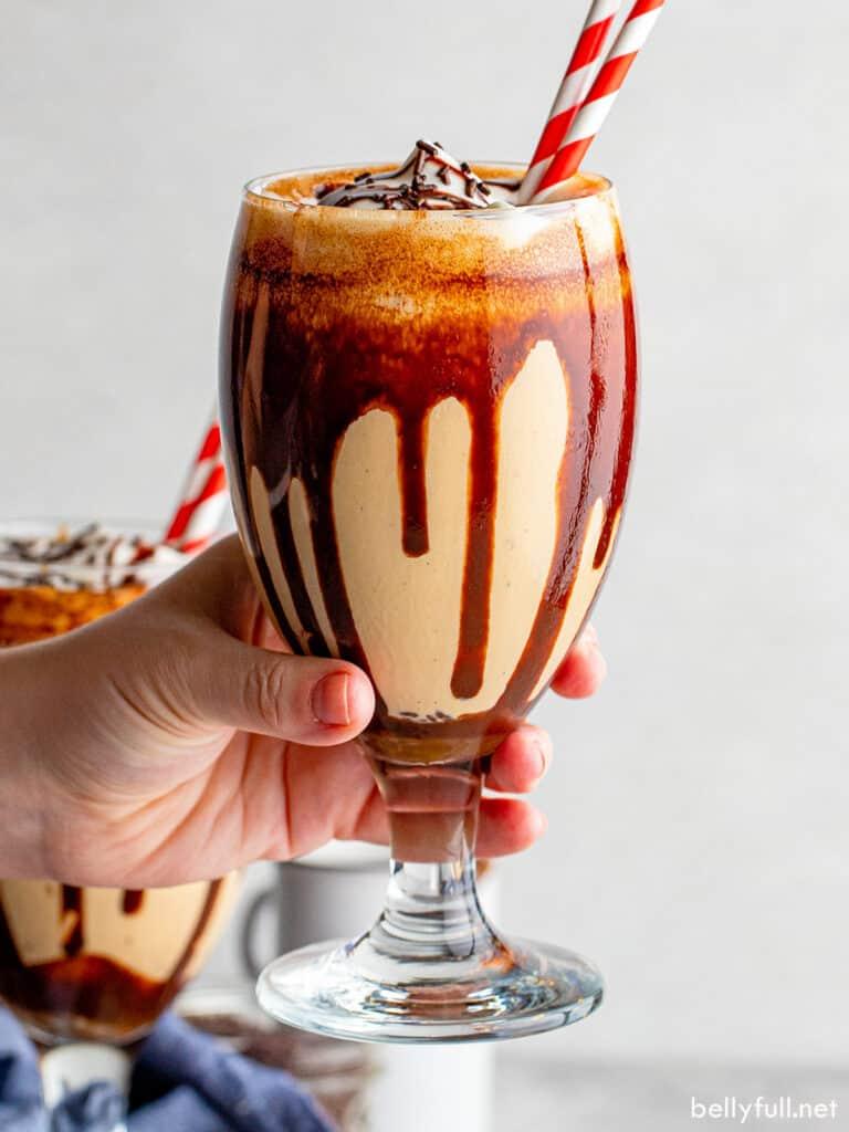 hand holding glass filled with mudslide milkshake