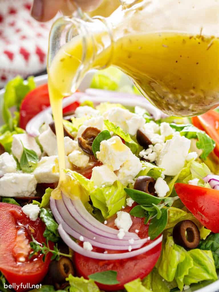 vinaigrette dressing being poured over Greek salad