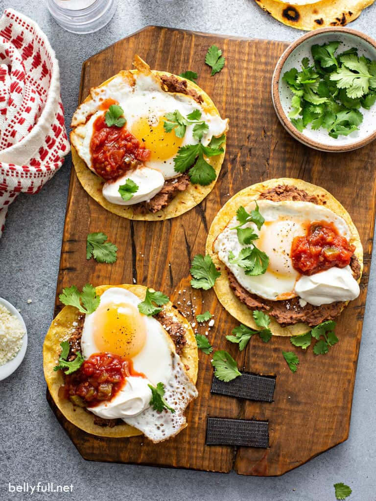 overhead 3 corn tortillas with black beans and fried eggs on wooden board