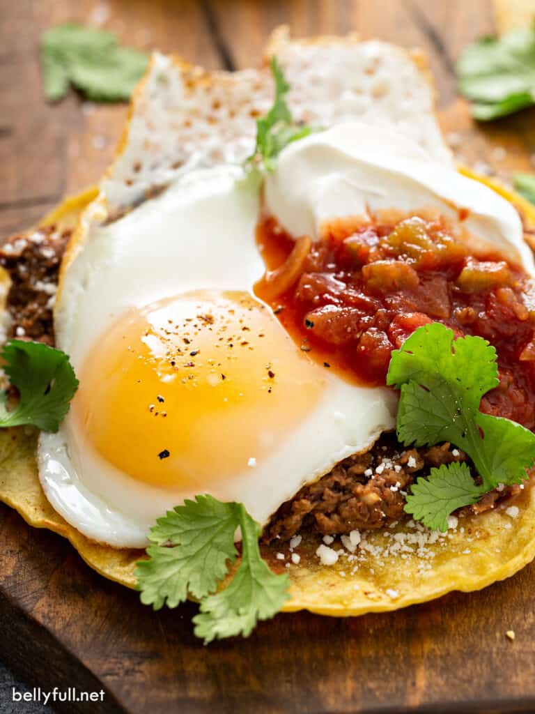close up fried egg with refried beans and salsa on corn tortilla
