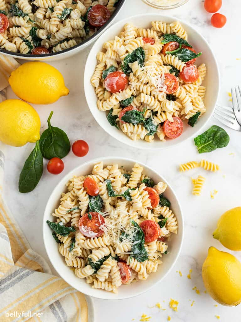 lemon pasta with tomatoes and spinach in 2 white serving bowls