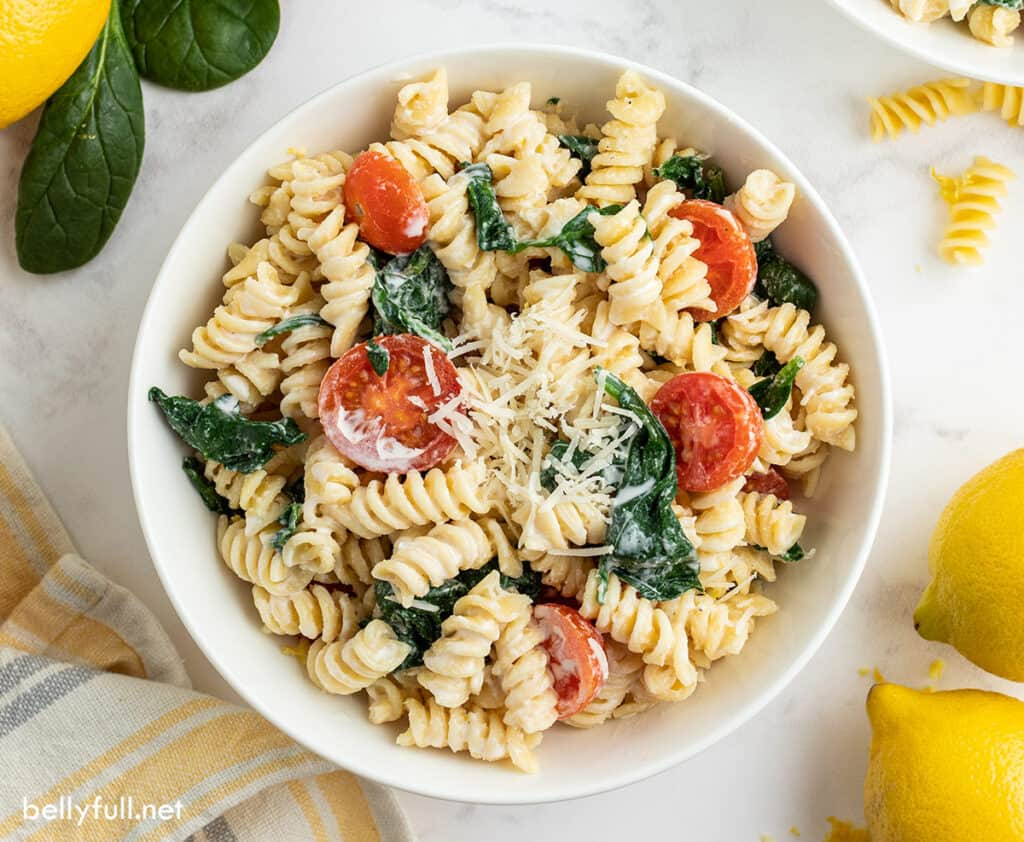 overhead picture of rotini pasta with tomatoes and spinach in white bowl