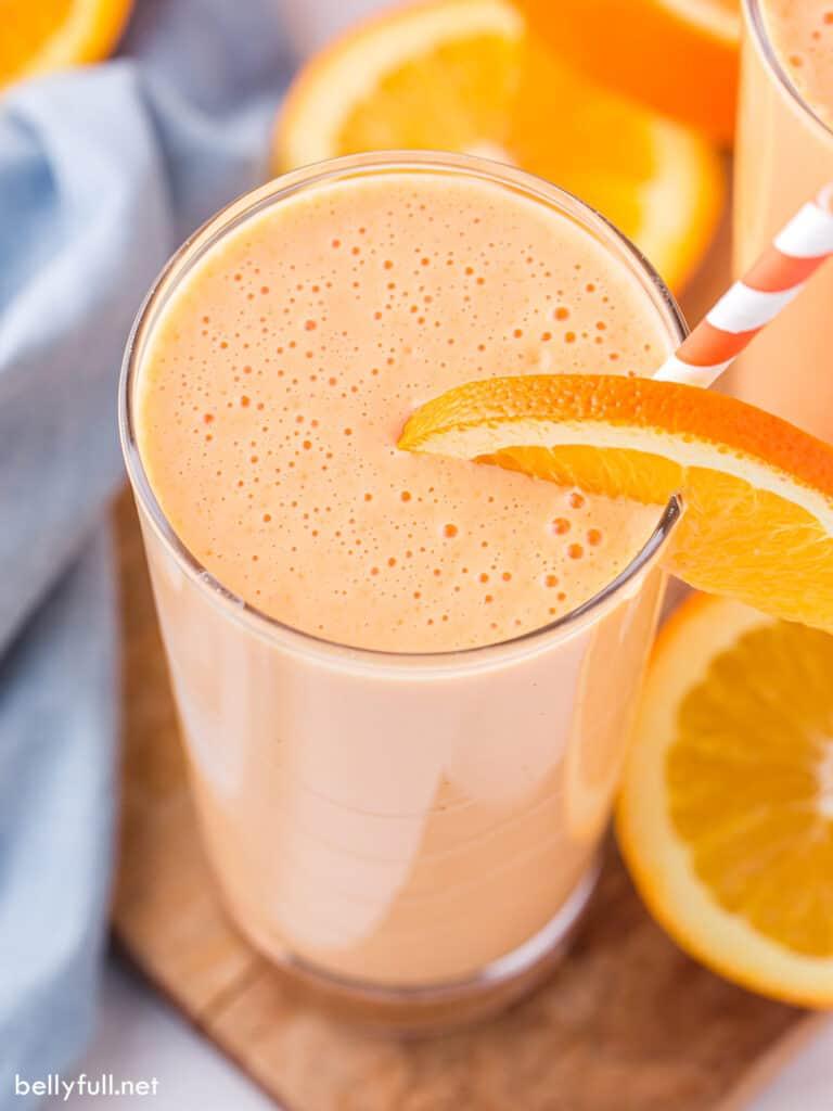 Orange Julius in tall glass with orange slice and straw