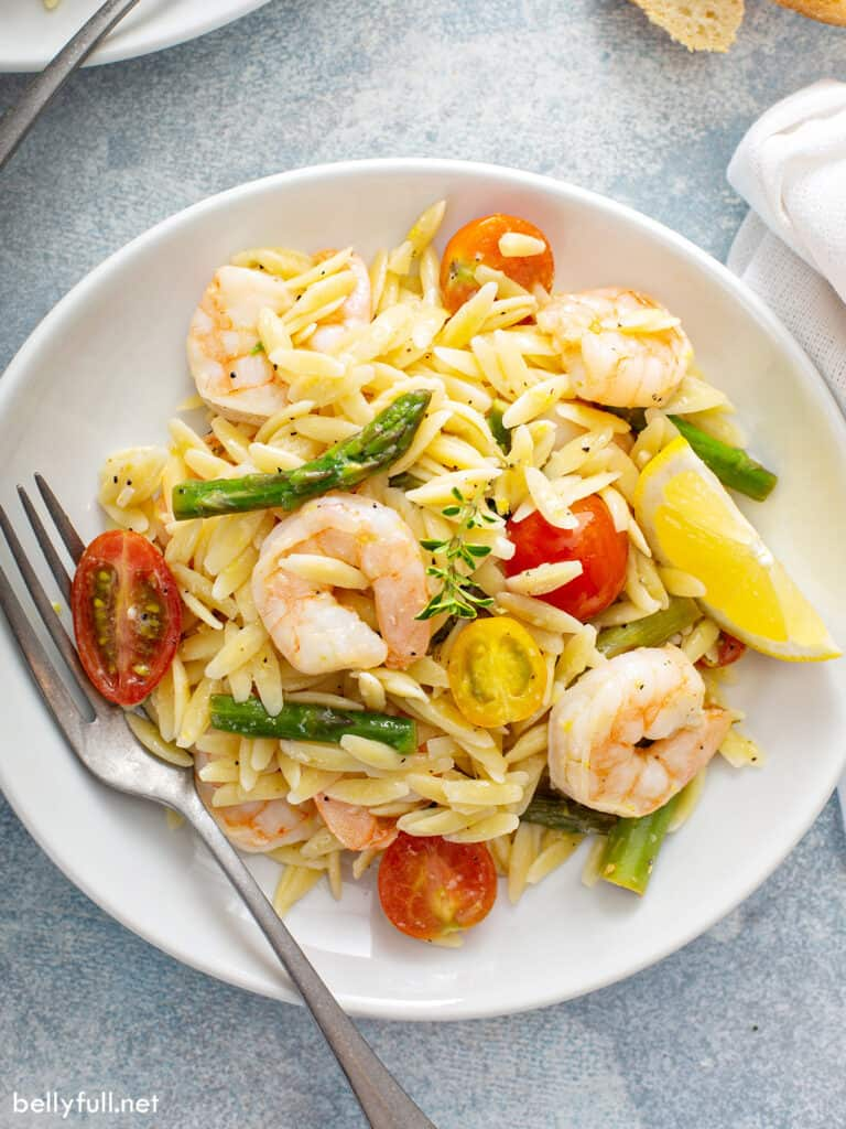 overhead of Orzo Pasta Salad with shrimp and asparagus on white plate