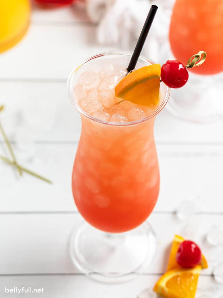 drink in a hurricane glass garnished with a cherry and orange slice