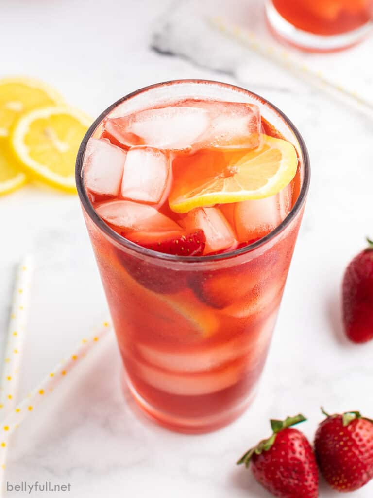 tall glass of strawberry tea with ice and a lemon slice