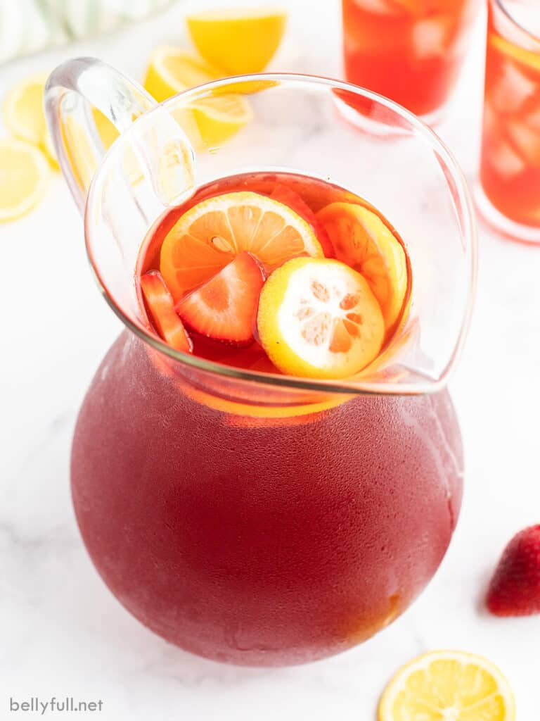strawberry tea in glass pitcher with lemon slices