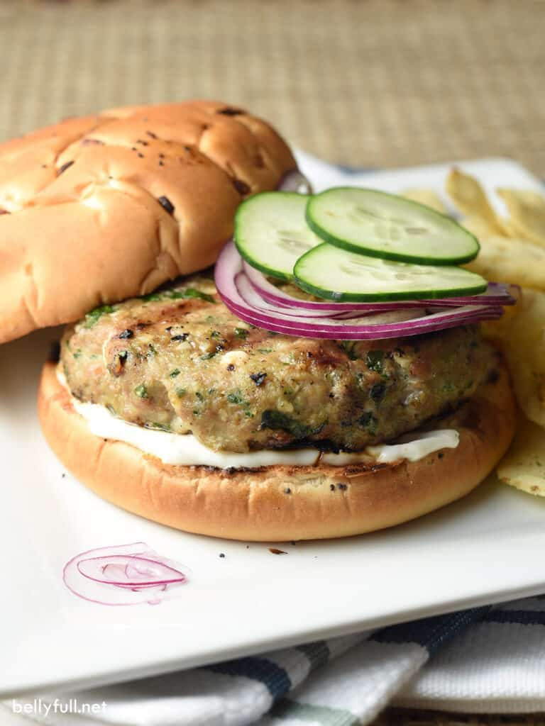 turkey burgers on bun with red onion and cucumber slices