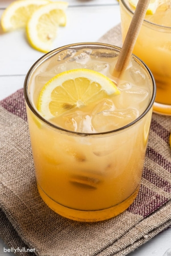Bee's Knees drink with half moon lemon slice and honey drizzler