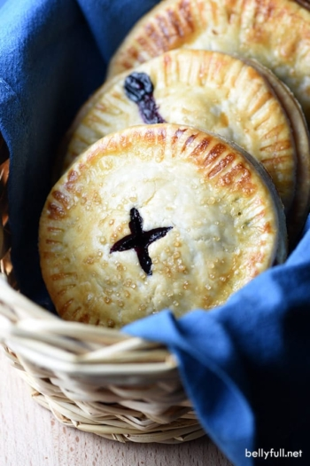Blueberry hand pies in basket with blue cloth napkin