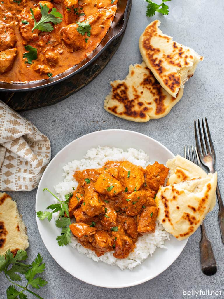 tikka masala over white rice on plate with torn naan