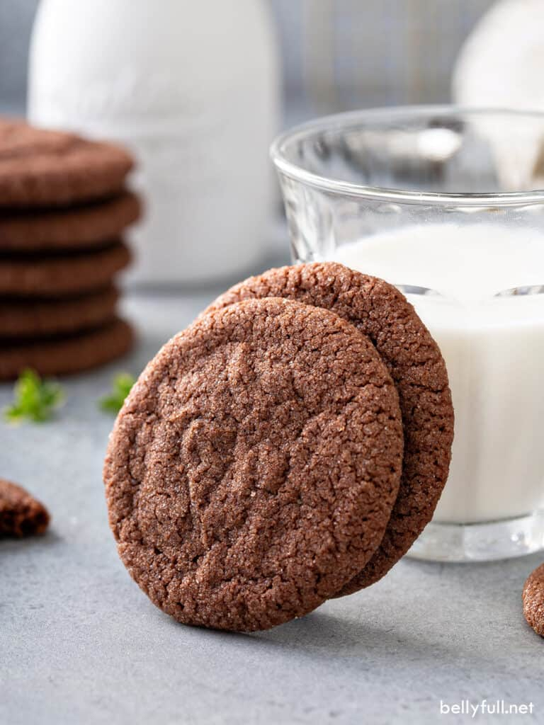 2 chocolate cookies resting on glass of milk