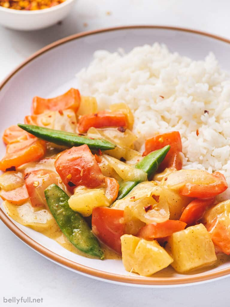 close up coconut curry veggie stir fry on plate with rice