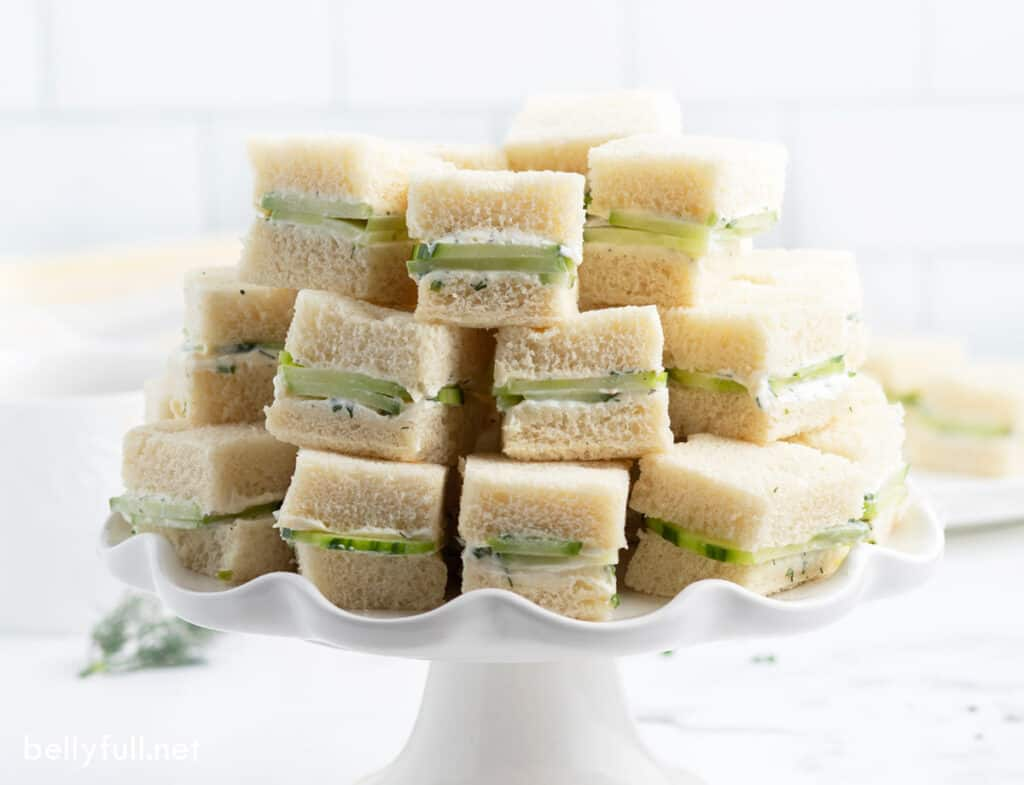 stacked tea sandwiches on white serving tray