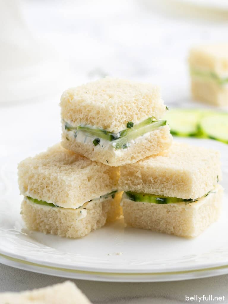 3 stacked cucumber sandwiches on white plate
