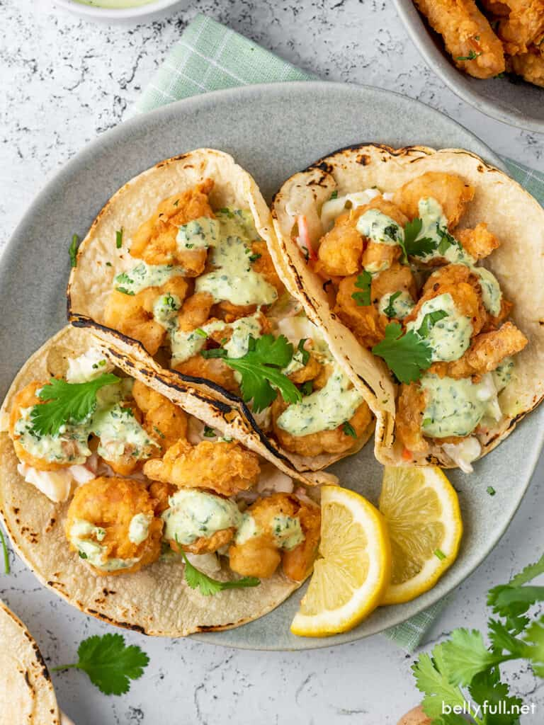 overhead view of 3 shrimp tacos on plate with lemon wedges
