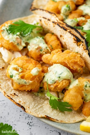 Fried shrimp tacos in corn tortillas with creamy dressing close up