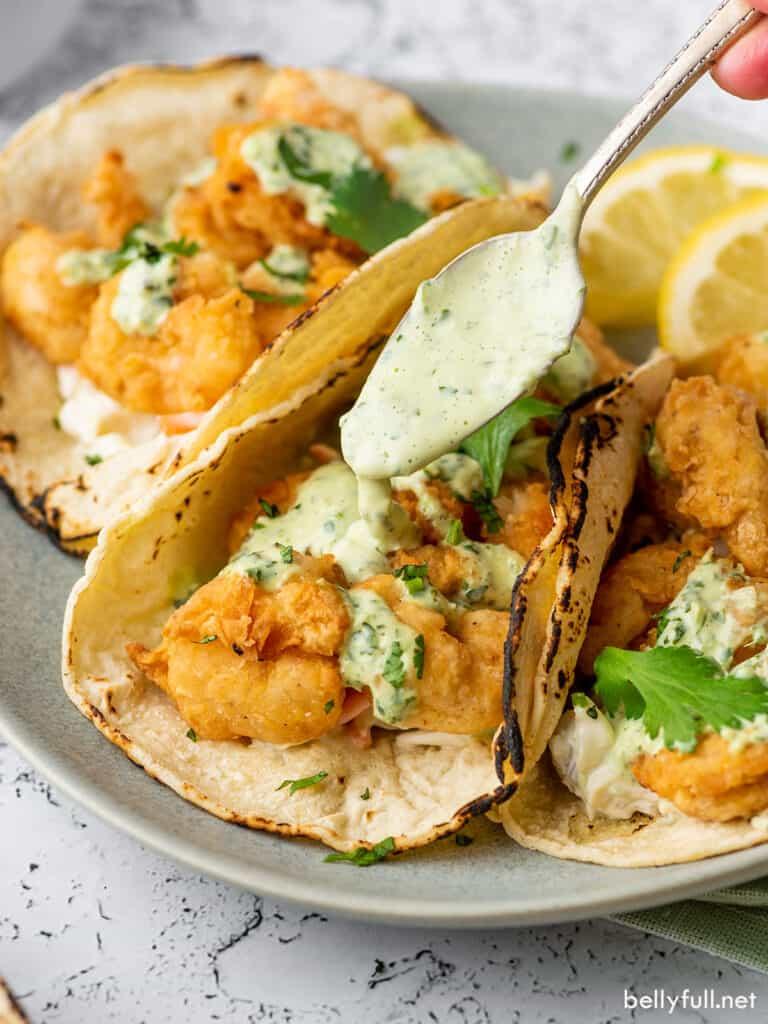 spoon drizzling creamy dressing over popcorn shrimp taco