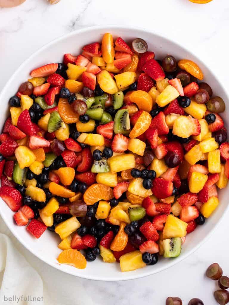 overhead summer fruit salad in white serving bowl