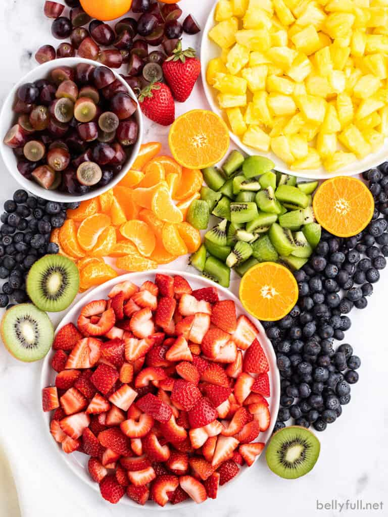 variety of fresh chopped summer fruits on cutting board