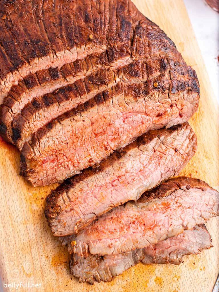 sliced grilled medium rare steak on cutting board