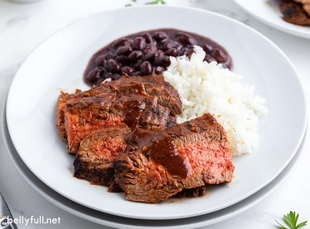sliced steak with sauce, rice, and black beans on white plate
