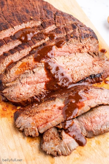 Sliced grilled flank steak with sauce on cutting board