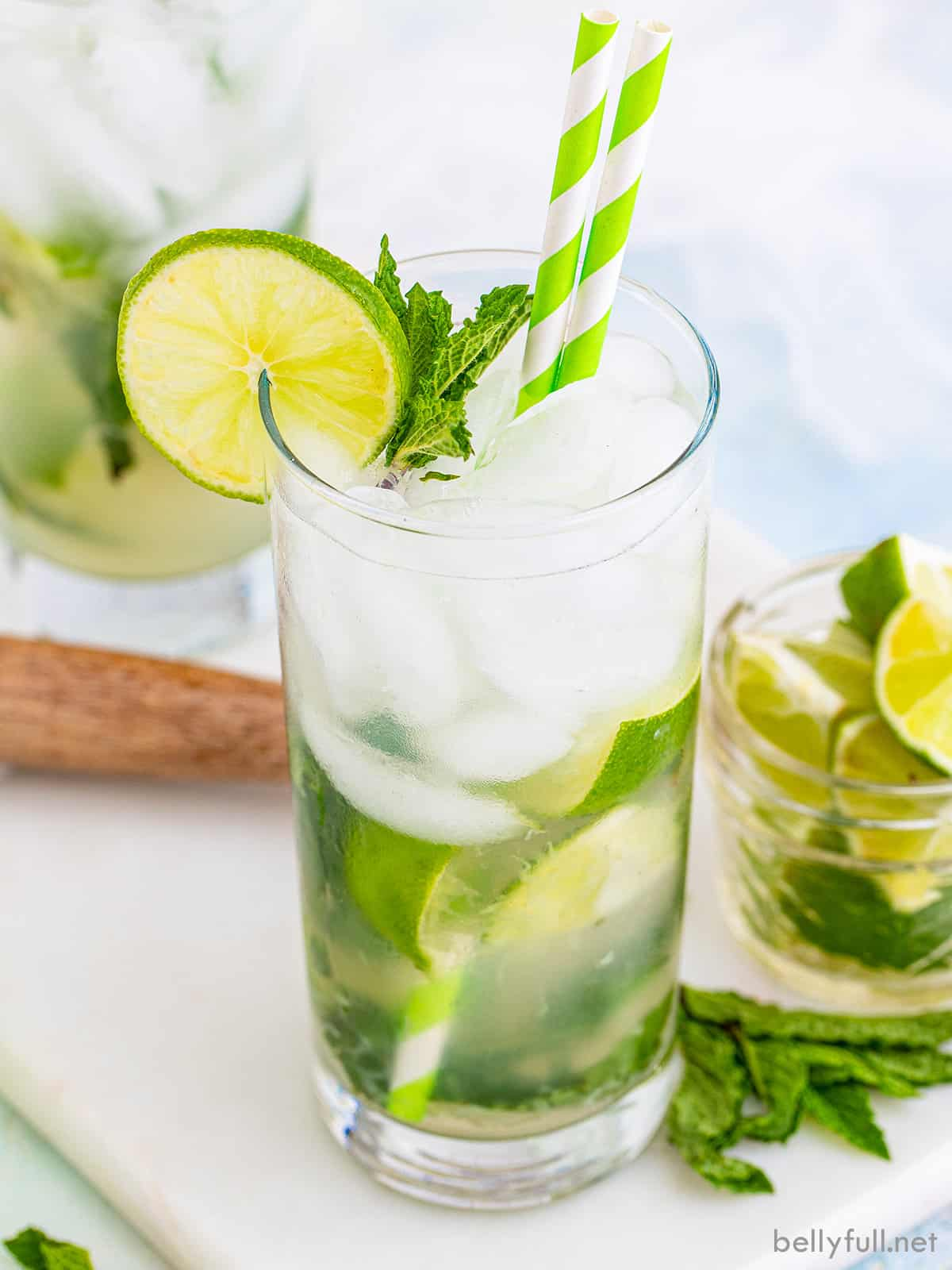 A classic mojito adorned with a green and white straw