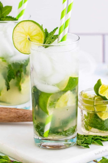 A classic mojito with a small glass of lime wedges to the side