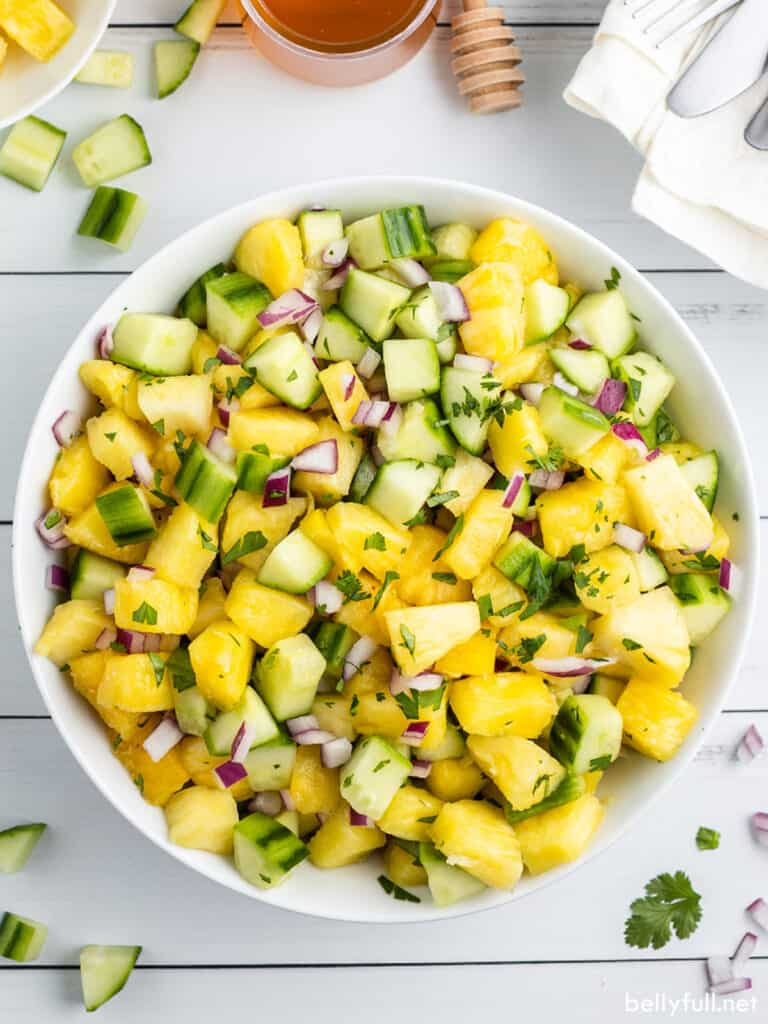 overhead view of pineapple cucumber salad in white serving bowl