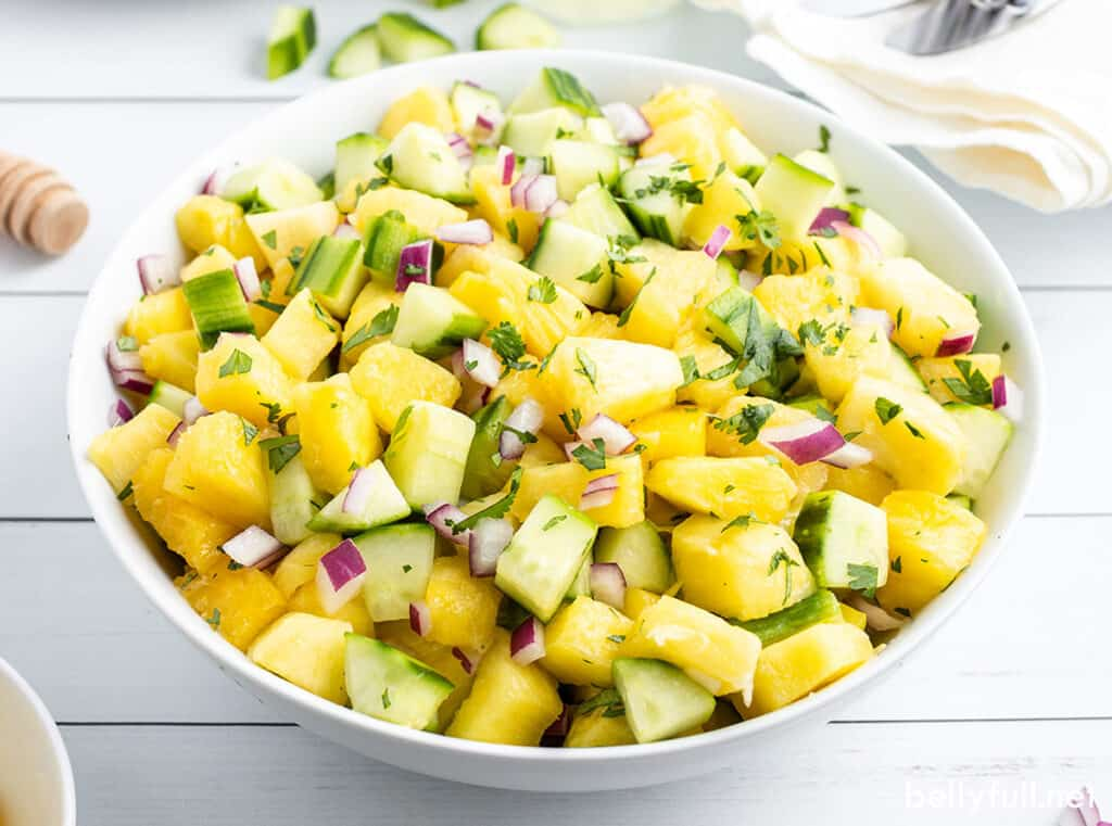 pineapple cucumber salad in white serving bowl
