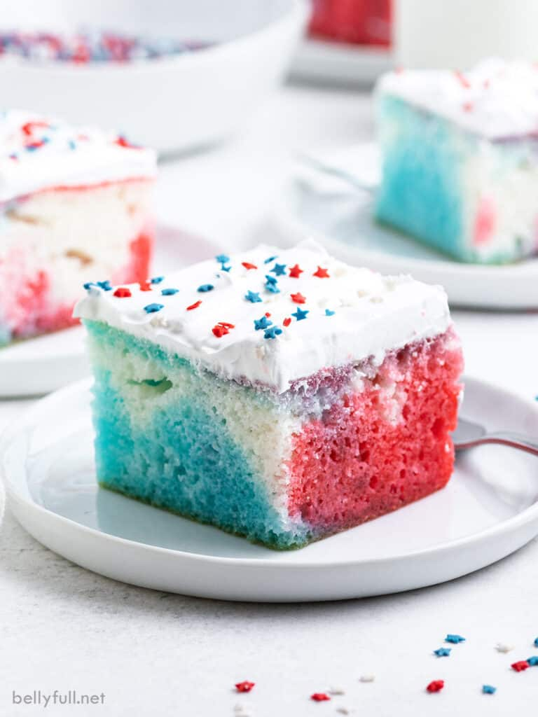 A slice of red white blue poke cake on a white plate