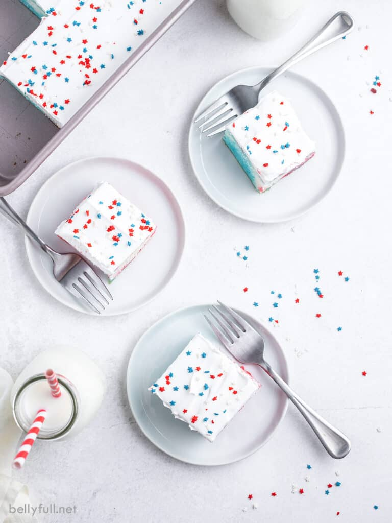 3 slices of red white and blue poke cake on white plates, topped with cool whip and sprinkles