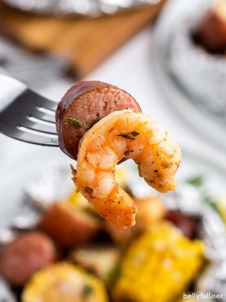 smoked sausage and shrimp on fork close up