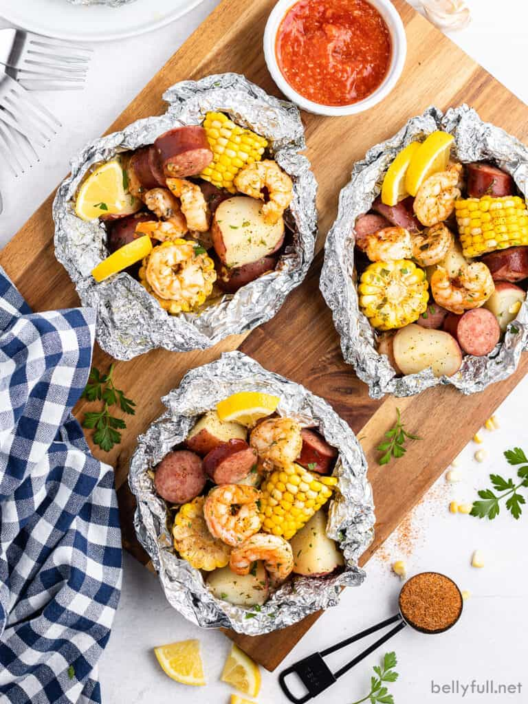 overhead view of 3 shrimp boil foil packets on cutting board