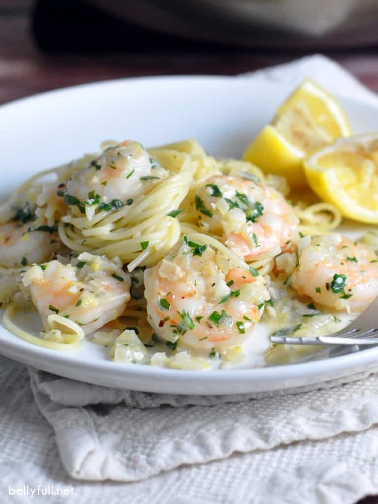 shrimp scampi with pasta on white plate