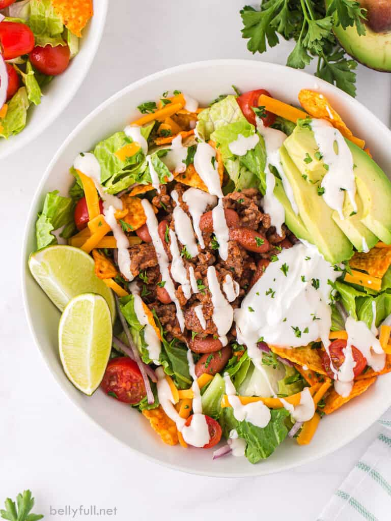 Mexican salad with ground beef drizzled with Ranch dressing