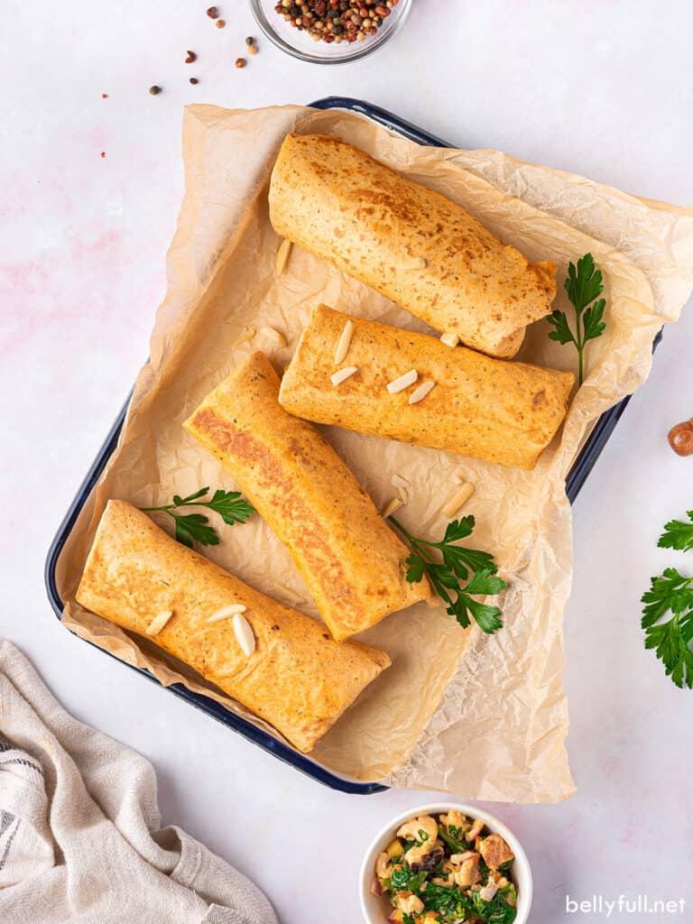 overhead 4 burritos on parchment paper