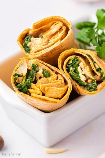 3 half chicken wraps in white basket