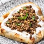 turkey keema on top of yogurt naan bread on ornate plate