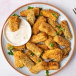 Aerial view of a plate of fried zucchini with a small dish of ranch dip