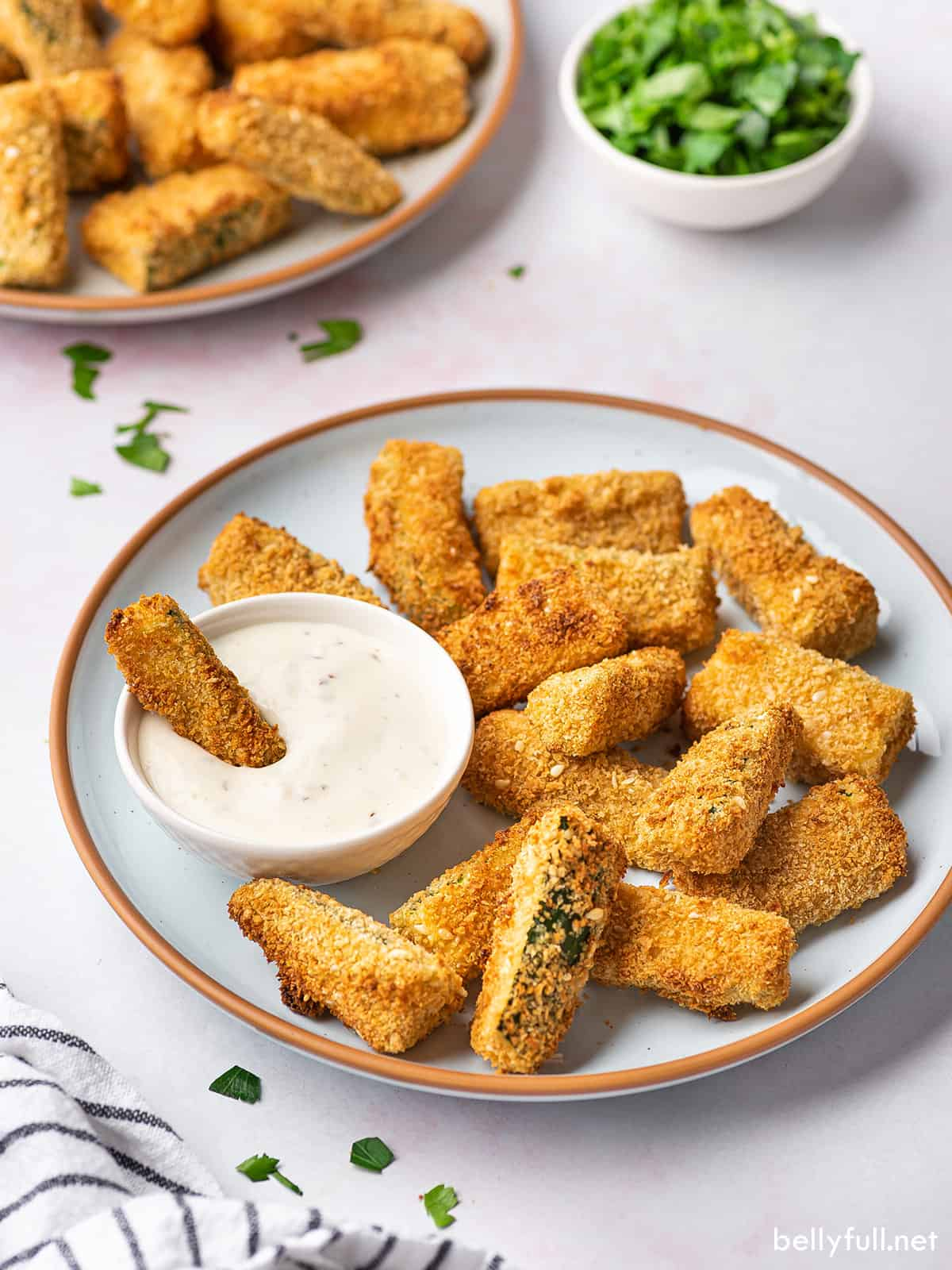 A plate of air fryer zucchini fries with one dipped into ranch dip