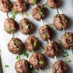 overhead view of beef kofta kebob meatballs on metal skewers