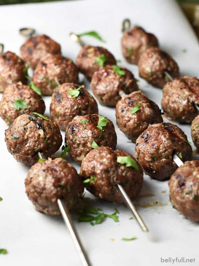 beef kebob meatballs on metal skewers sprinkled with parsley