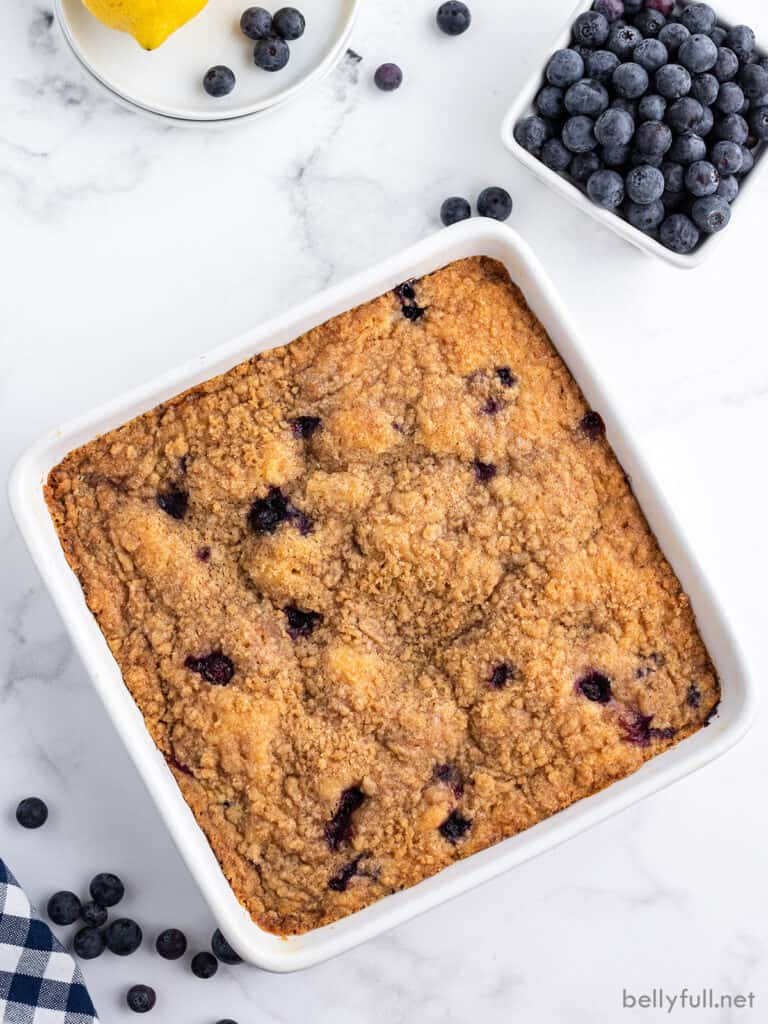 overhead baked coffee cake in white pan with cup of fresh blueberries