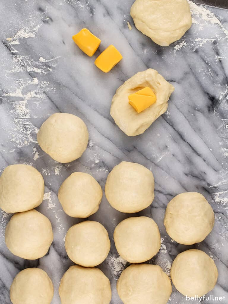 raw dough rolls being stuffed with cubes of cheese