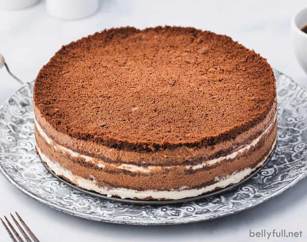 uncut chocolate layered cake on ornate plate