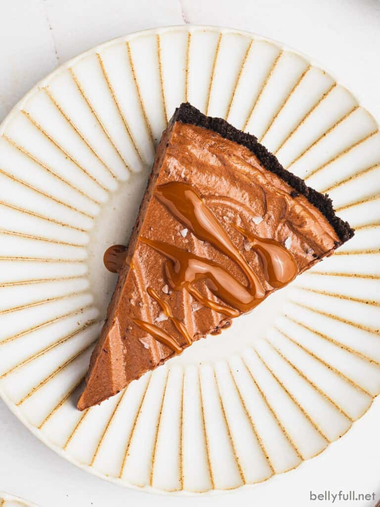 overhead slice of chocolate mousse pie drizzled with caramel on ornate plate